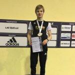 Athlet auf Siegerpodest mit Urkunde