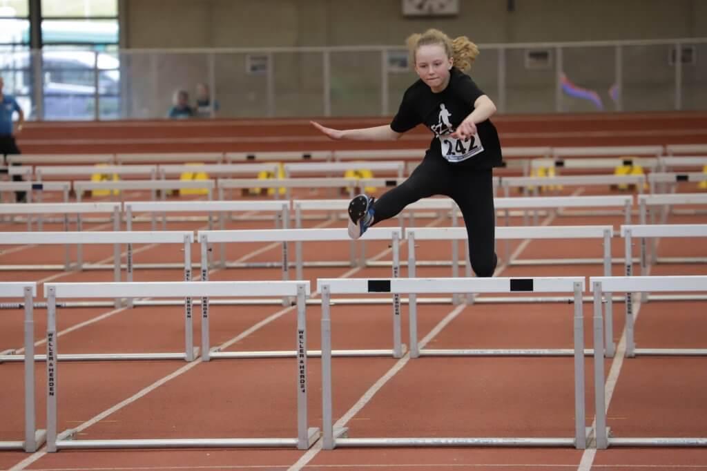 Junge Sportlerin beim Hürdenlauf